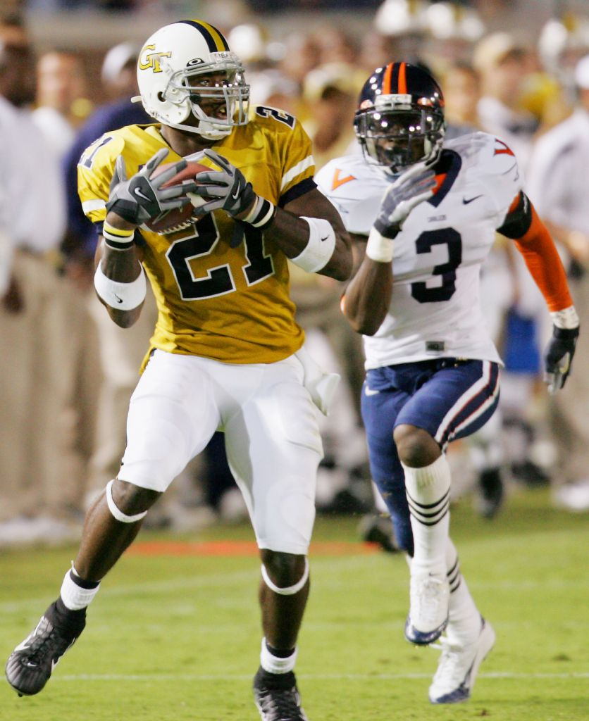 Georgia Tech wide receiver Calvin Johnson (21) pulls down a second-half pass in front of Virginia cornerback Marcus Hamilton (3) on the way to scoring a touchdown. (AP Photo/Ric Feld)