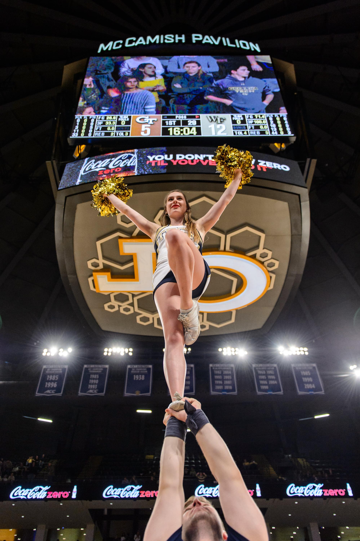 A Georgia Tech Cheerleader stunts for the fans